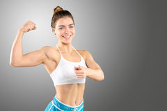 Sporty woman demonstrating biceps Stock Images