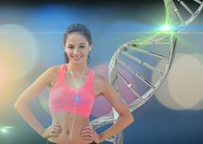 Sporty woman with dna chain behind her. Blue lights background. Digital composite of sporty woman with dna chain behind her. Blue lights background royalty free stock photography