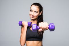 Sporty woman does the exercises with dumbbells on white background. Muscular woman in sportswear on white background. Strength and stock image