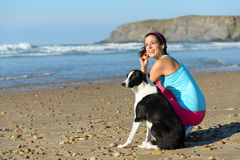 Sporty woman and dog on beach Royalty Free Stock Images