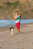 Sporty woman and dog running at beach Stock Photo