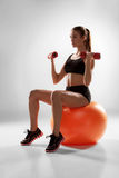 Sporty woman doing aerobic exercise. With red dumbbells on a fitness ball on grey background stock images