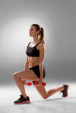 Sporty woman doing aerobic exercise. With red dumbbells on grey background stock image