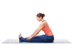 Sporty woman doing Ashtanga Vinyasa yoga asana. Sporty fit woman doing Ashtanga Vinyasa yoga back bending asana Paschimottanasana - seated forward bend beginner Stock Image