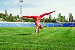 Sporty woman doing cartwheel on stadium Royalty Free Stock Photography