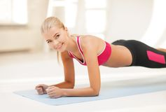 Sporty woman doing exercise on the floor Stock Photos