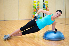 Sporty woman doing exercises for abdominal muscles on bosu ball. In gym Royalty Free Stock Photos