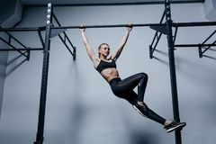 Sporty woman doing exercises on a horizontal bar in the gym Stock Image