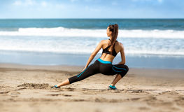Sporty woman  doing exercising on sand coast Stock Images