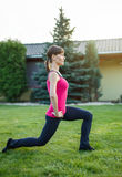Sporty woman doing lunge exercise in sunset Stock Photography