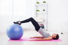 Sporty woman doing pilates exercise lifting her Stock Photo