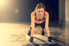 Sporty woman doing plank exercise with dumbbells royalty free stock photography