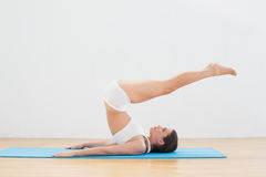 Sporty woman doing the plough posture on exercise mat Royalty Free Stock Photo