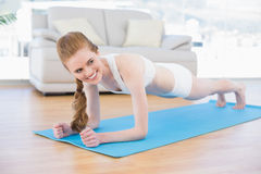 Sporty woman doing push ups in fitness studio Royalty Free Stock Images
