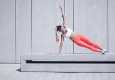 Sporty Woman Doing Side Plank Exercise on Platform Stock Photo