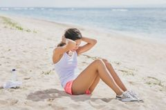 Sporty woman doing sit up at the beach stock image