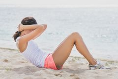 Sporty woman doing sit up at the beach stock photography