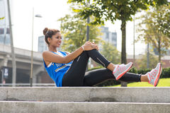 Sporty woman doing stretches before exercising in the park. Royalty Free Stock Images