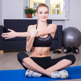 Sporty woman doing stretching exercise at home Royalty Free Stock Photography