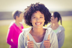 Sporty woman doing thumbs up in front of friends Royalty Free Stock Photo