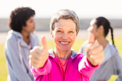 Sporty woman doing thumbs up in front of friends. Portrait of sporty women doing thumbs up in front of friends in parkland Stock Photo