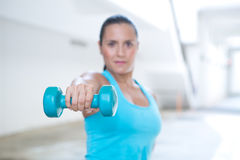 Sporty woman doing triceps extension. Only hand and dumbbell in focus. Stock Images