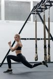 Sporty woman doing TRX exercises in the gym Royalty Free Stock Photos