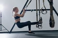 Sporty woman doing TRX exercises in the gym Royalty Free Stock Photo