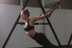 Sporty woman doing TRX exercises in the gym Royalty Free Stock Image