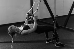 Sporty woman doing TRX exercises in the gym Stock Photography