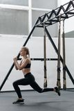 Sporty woman doing TRX exercises in the gym Royalty Free Stock Images