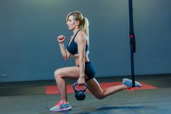 Sporty woman doing TRX and weight exercises in the gym royalty free stock photos