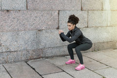 Sporty woman doing warm up squat stock photos