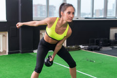 Sporty woman doing work-out swinging kettlebell in gym. royalty free stock photo