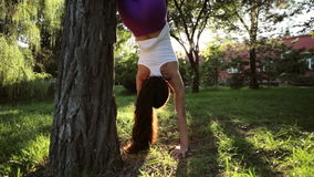 Sporty woman doing yoga exercises with handstand headfirst near the tree. stock video footage
