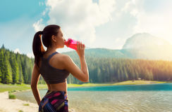 Sporty woman drink water, training on lake shore Royalty Free Stock Photos