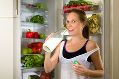 Sporty woman drinking milk for healthy nutrition in the kitchen Stock Image