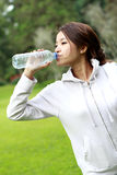 Sporty woman drinking mineral water during break after workout Royalty Free Stock Image
