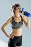 Sporty woman drinking water from bottle after training Royalty Free Stock Photo