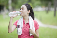 Sporty woman drinking water after jogging Stock Photos