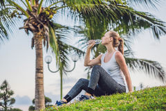 Sporty woman drinking water outdoor on sunny day Royalty Free Stock Photography