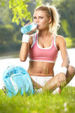 Sporty woman drinking water after training Royalty Free Stock Image