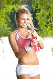 Sporty woman drinking water after training Stock Photo