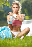 Sporty woman drinking water after training Stock Image