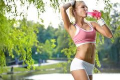 Sporty woman drinking water after training Royalty Free Stock Images