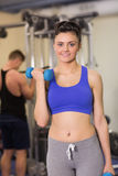 Sporty woman with dumbbell amd man using lat machine in the gym royalty free stock photo