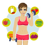 Sporty woman with dumbbells and variety of healthy fruits. Sporty young woman with dumbbells and variety of healthy fruits Royalty Free Stock Photos