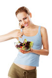 Sporty woman is eating a healthy salad smiling isolated. On white Stock Photography