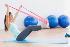 Sporty woman with exercise band in fitness studio. Full length side view of a sporty young woman with exercise band in fitness studio Stock Image