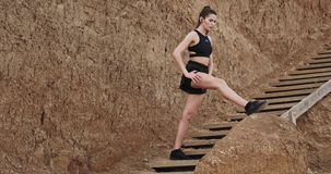 Sporty woman exercises on wooden steps outside stretching the legs wearing sportswear , listening music from wireless. Headphones. slow stock video footage